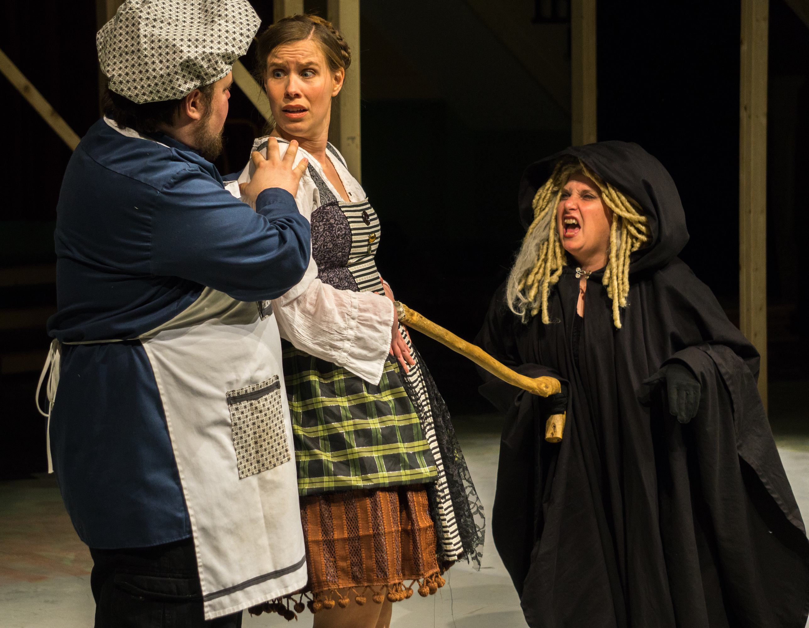 The Witch (cloaked in black) threatens The Bakers Wife (Carolyn Wesley in multi-colored, short skirted peasant outfit) by lunging at her with her magic cane, while the Baker (Nick Wheeler, in polka dotted baking cap & matching apron) tries to protect his wife